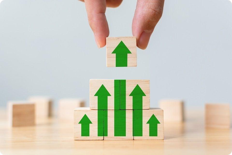 Lean Manufacturing - 4 blocs de couleurs vives de différentes hauteurs disposés à la verticale, sur lesquels sont positionnées des échelles qui permettent d'atteindre le sommet. Etape par étape avec des plateaux intermédiaires.