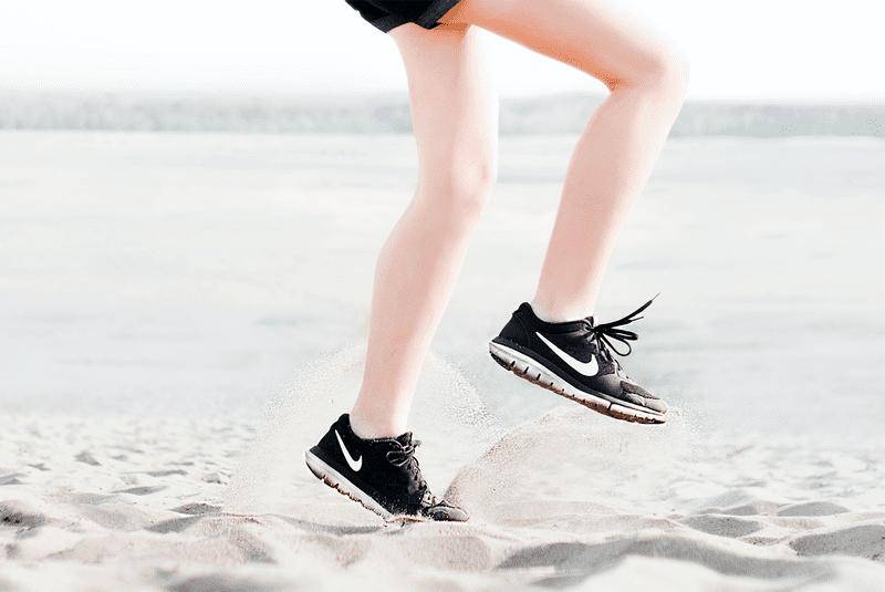 woman's legs running on sand