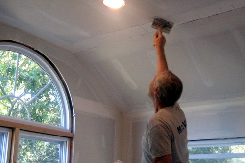drywall contractor spackling a ceiling