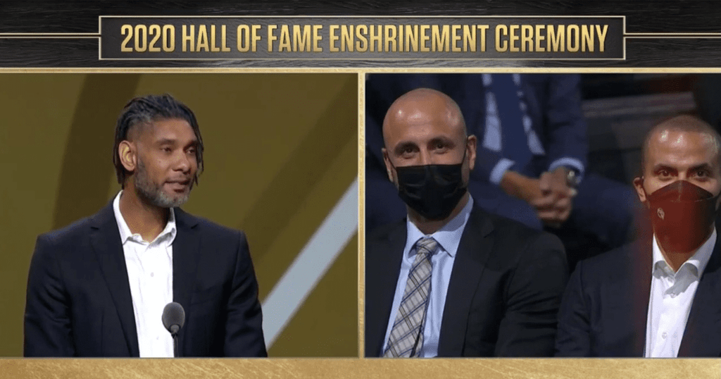 An image of Tim Duncan, Manu Ginobili, and Tony Parker at the 2021 Basketball Hall of Fame Enshrinement Ceremony with a black and gold border and gold lettering
