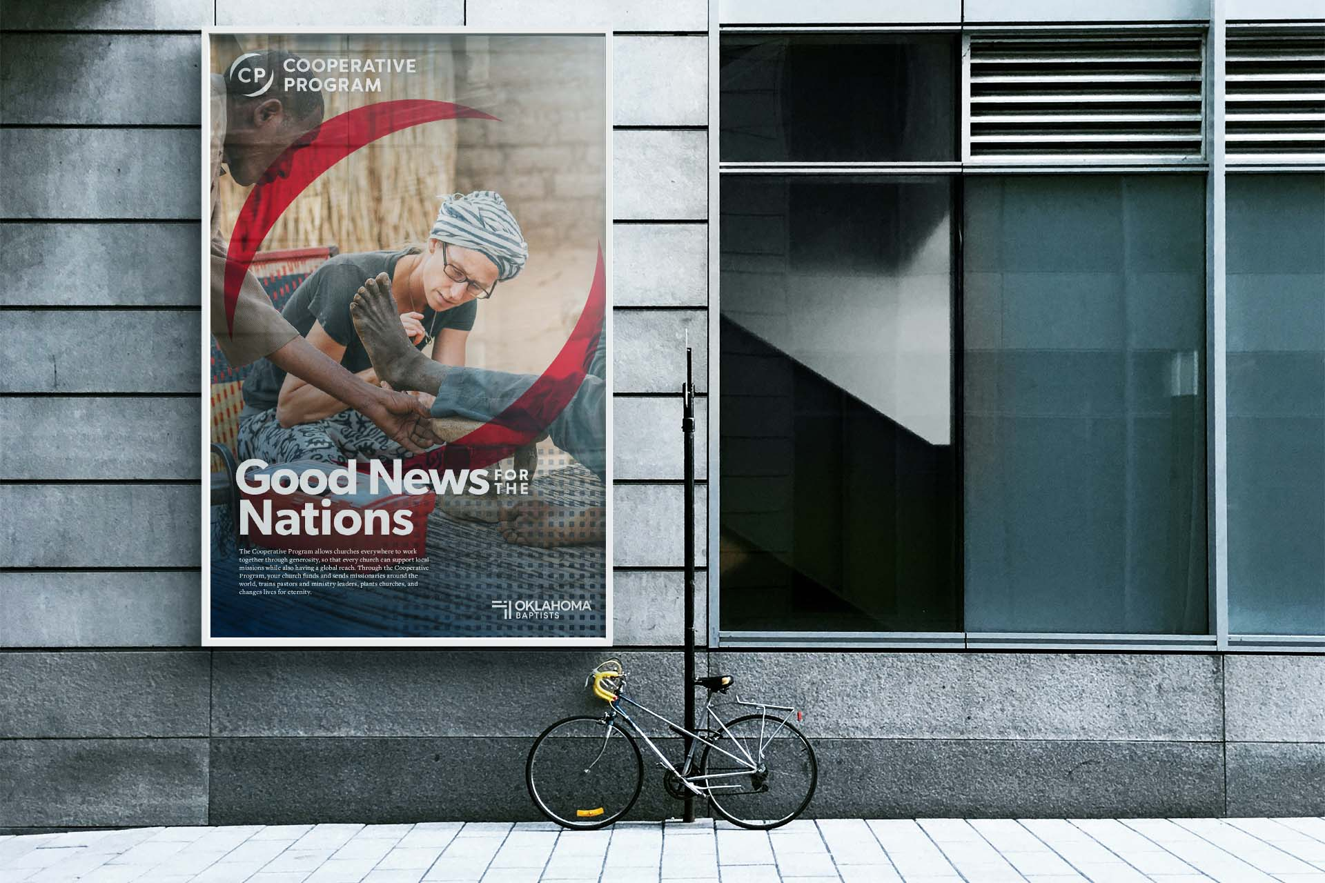 A poster mounted to the side of a building, depicting a missionary doctor examining a patient.