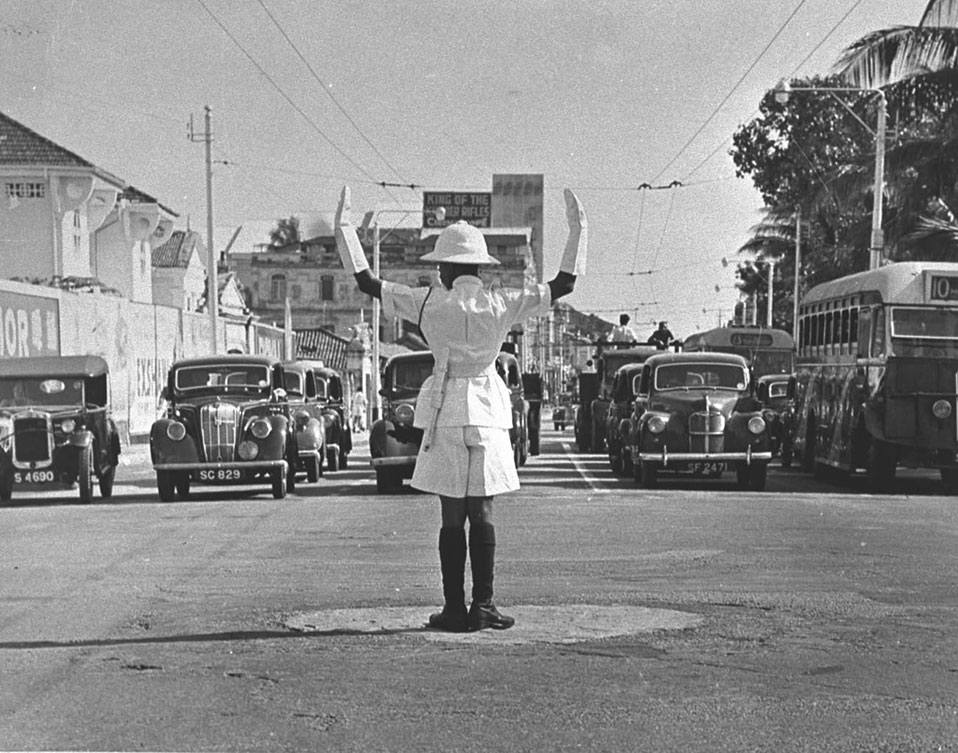 A traffic policeman guiding vehicles at a junction, 1950s