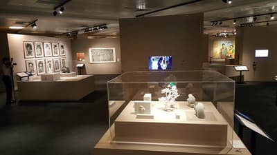 A photo overview of the exhibition. There are sculptures and paintings. A small TV screen is in a wall.