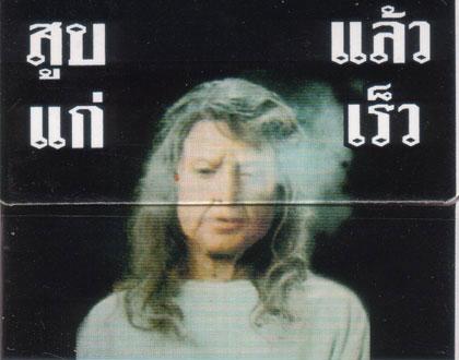 """Rauchen ist böse. Und Thailand ist das wohl konsequenteste Land in der Bekämpfung der Raucher ;) Seit April dürfen Zigarettenpackungen nicht mehr öffentlich zum Verkauf angeboten werden. In den meisten Läden wurde das so geregelt, dass die Regale mit den Zigarettenschachteln hinter kleinen Klappen versteckt werden.   Nur bei 7Eleven nicht, die gehören wohl irgendwie Premierminister Thaksin und wehrten sich vehement gegen die Verordnung. Bis vergangene Woche, wo das Gesundheitsministerium eine Razzia machte, ein paar Leute einkassierte und bestimmte, dass bis nächste Woche auch da die Zigaretten versteckt werden.   Feine Sache.   Auf den Schachteln stehen übrigens nicht die in Europa beliebten Schwarzen Sätze sondern gleich unterhaltsame Bilder, was alles so passieren kann, wenn man raucht. Grund genug, eine neue kleine Serie anzufangen: Zigarettenbildchen.  Auf dem aktuellen Bild sehen wir eine, ehm, ältere Frau die raucht und übellaunig ist. Ich bin mir fast sicher, dass die zugehörige Aufschrift """"Wenn du rauchst kriegst du Falten und graue Haare"""" lautet. Ich werde am Wochenende mal meine Thaiculture-Quelle anzapfen."""