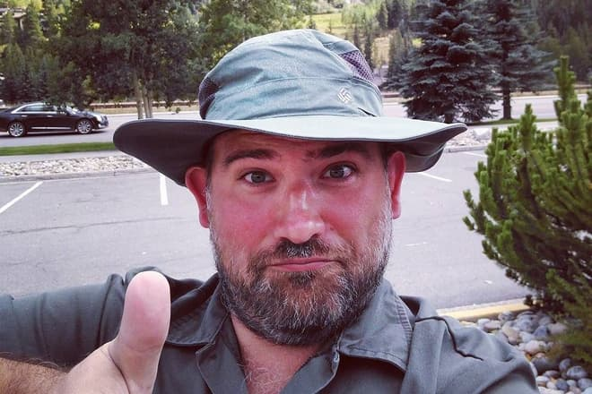 A selfie taken near Vail, Colorado. I am wearing a green soft-brim hat and a green shirt, and am making a weird face while giving a thumbs up.