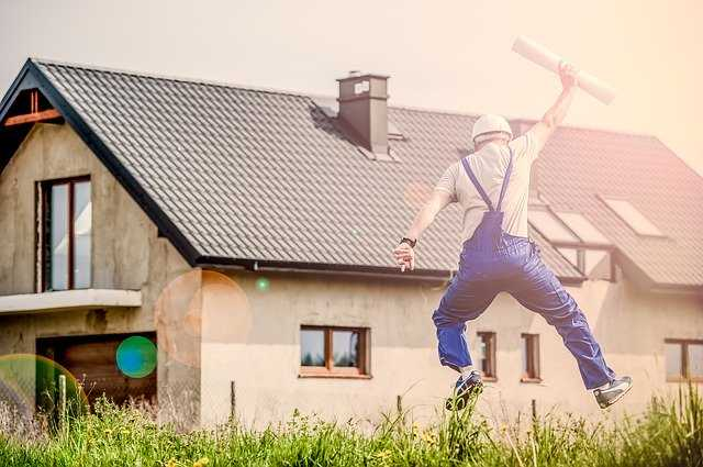 A construction worker jumping in front of a house