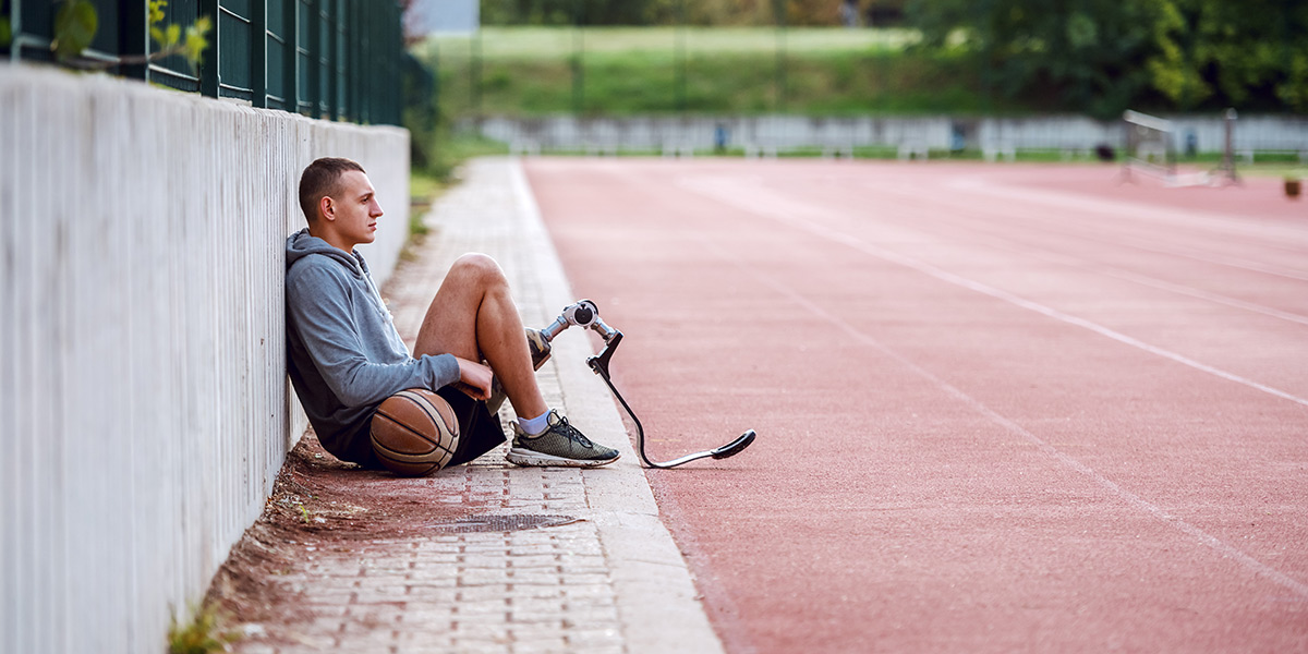 Athlete with a prosthetic leg, sitting at the edge of a running track.