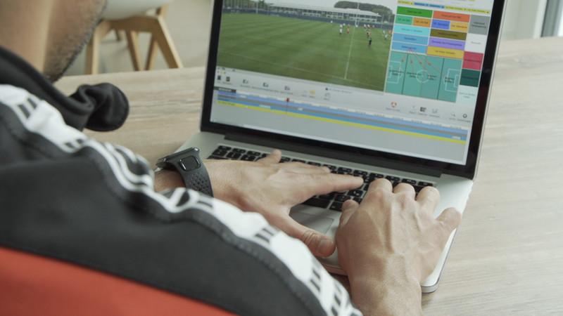 ノート PC で映像を分析するダニーロ・デ・ソウザの肩越しに画面を見る