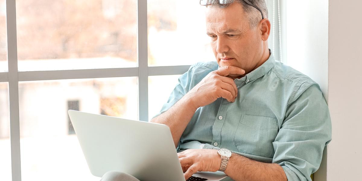 An aspiring data analyst reading something on a laptop