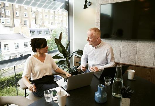 Personen arbeiten entspannt zusammen am Laptop.