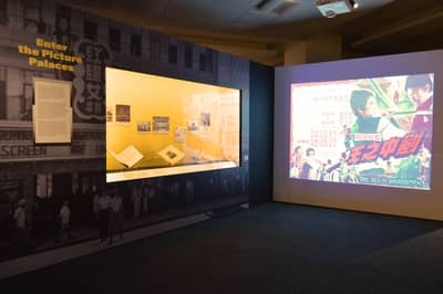 A photo of the Enter the Picture Palaces section. On the left wall, there is a showcase featuring books and images. On the right wall, there is a projection showing classic movie posters.