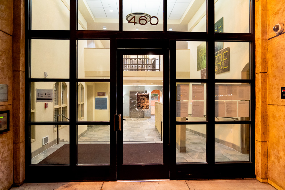 The glass on the front door of Avé Vista Apartment sits broken after several ground-level windows were smashed on the building during protests in Oakland, Calif., August 26, 2020. Residents said there were no residential units on the ground floor.