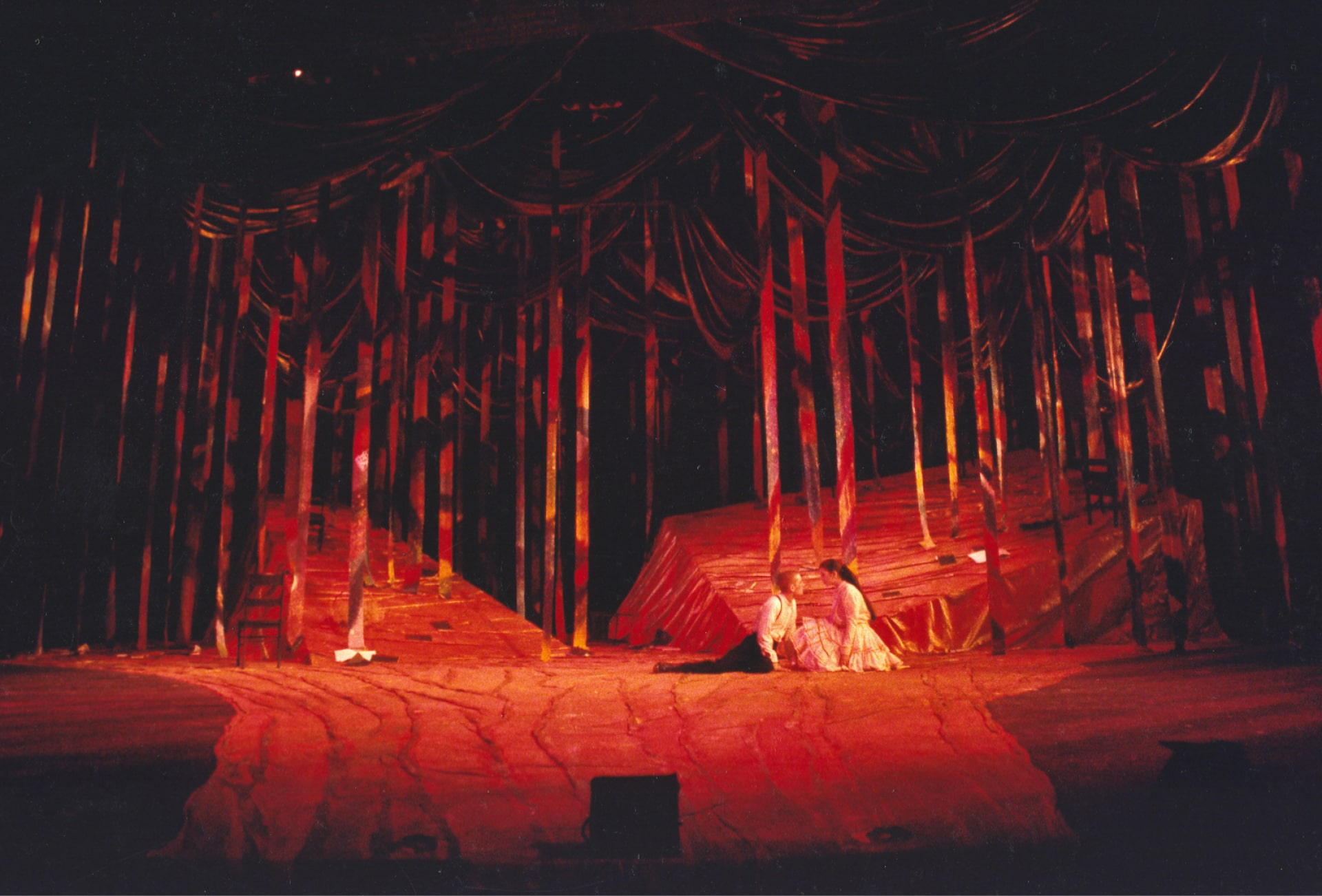 Young couple sits in red fabric forest.