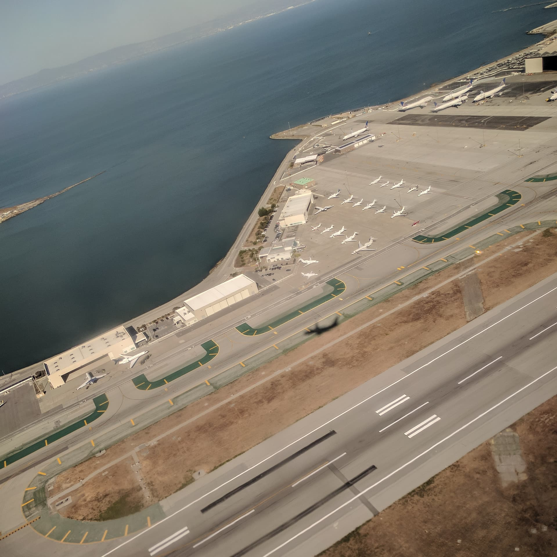 Runways and hangers at the San Francisco International Airport, as seen from a plane shortly after takeoff. San Francisco Bay can be seen in the background; the plane's shadow can still be distinctly seen near the center of the image.