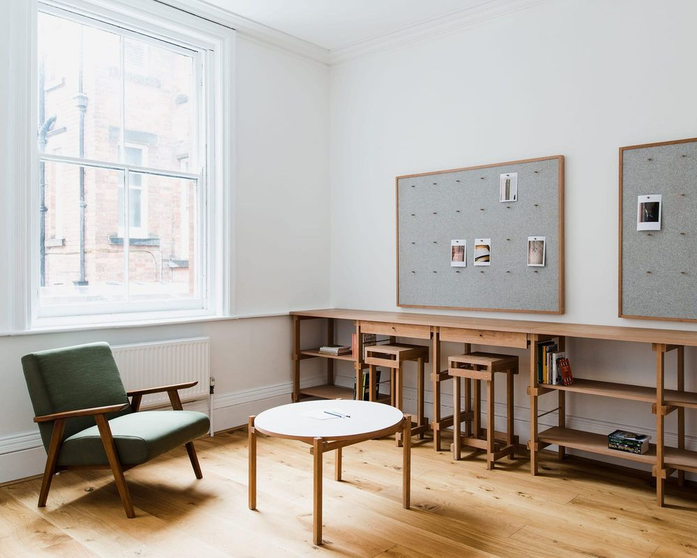 Interior view of the bespoke solid cherry, felt and brass fitted joinery and furniture designed by From Works at the National Justice Museum in Nottingham.