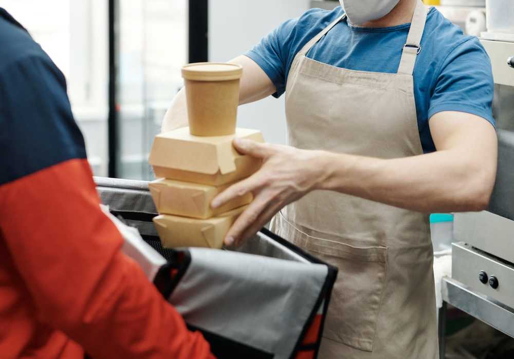 Restaurant worker hands food to delivery man. Article for Table Sage
