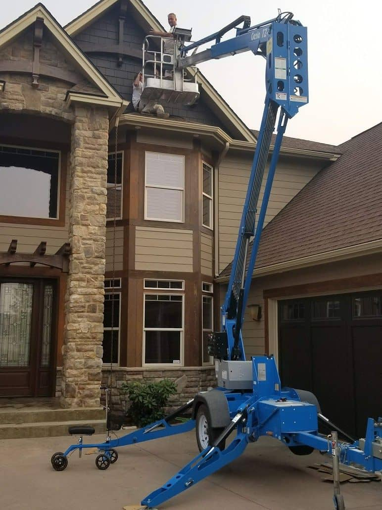 enlarged photo of man on crane lift painting a two story home
