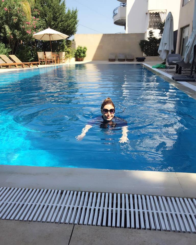 woman wearing sunglasses and smiling in swimming pool