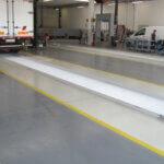 Corsie con colore a contrasto integrate nella pavimentazione in resina di un'officina padovana.
