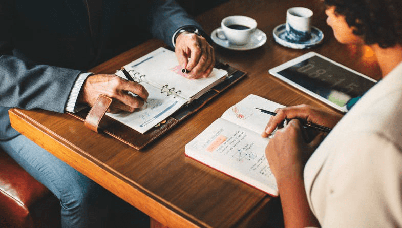 Colleagues, business owners, staff discuss aggressive and conservative business plans over wooden table with notebooks, pens and tablets #businessplanning