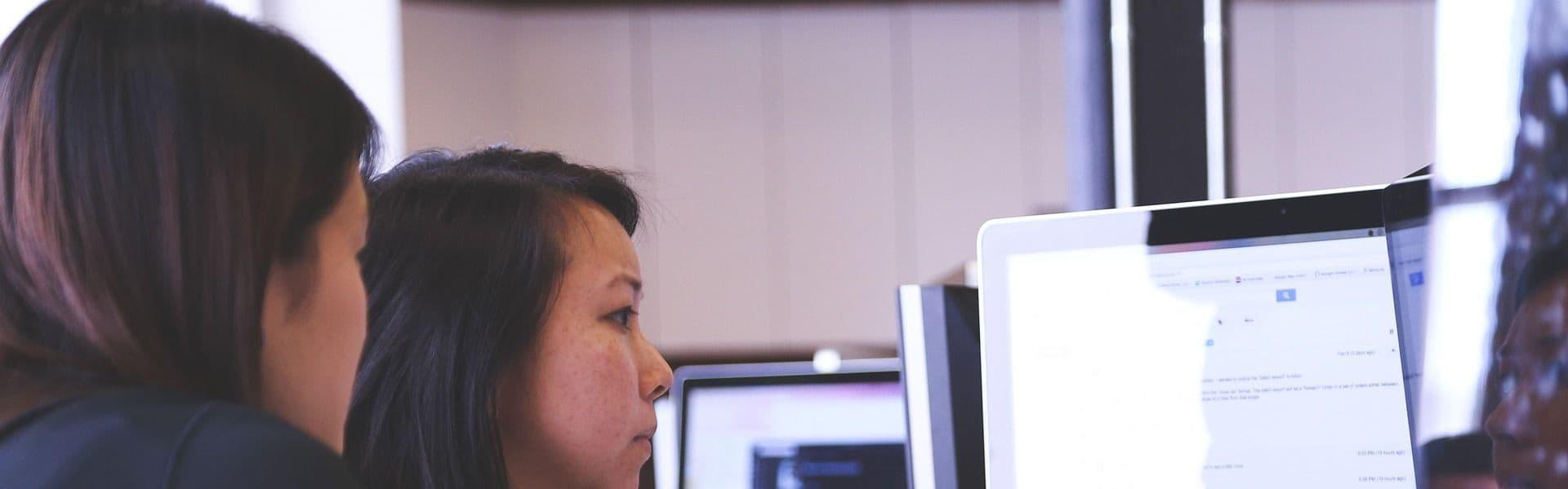 Trainerin hilft Teilnehmerin bei Training ob the Job an ihrem Computer