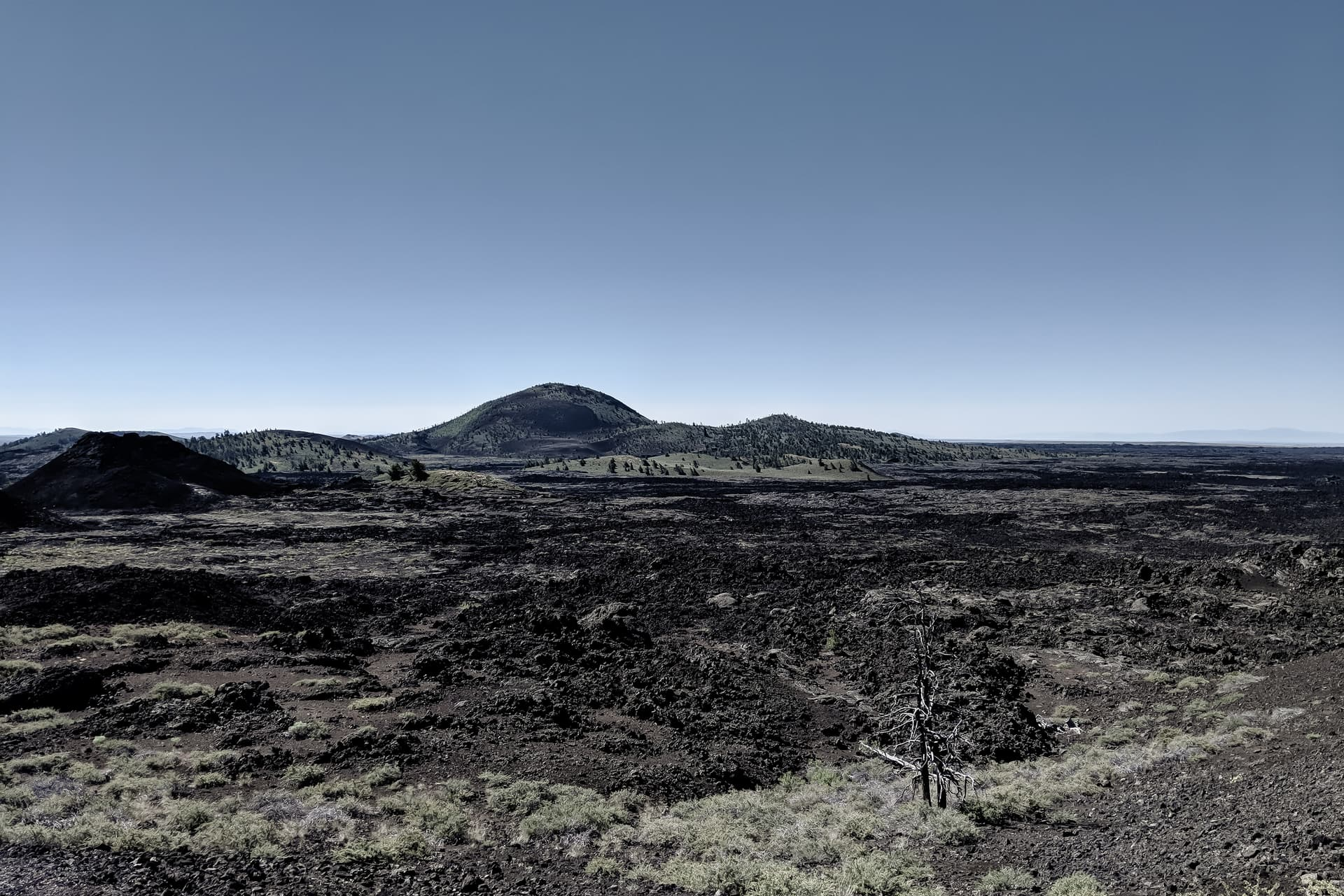Looking out across the top of a scrub-covered cinder cone across a dark lava flow and to another set of low cinder cones.