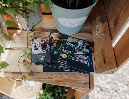 Flyer und Visitenkarten in dekorativen Holzkisten vor Blumen und Kerzen