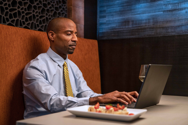 Vanderbilt student wearing a gold striped tie types on his laptop while having a meal in a restaurant booth