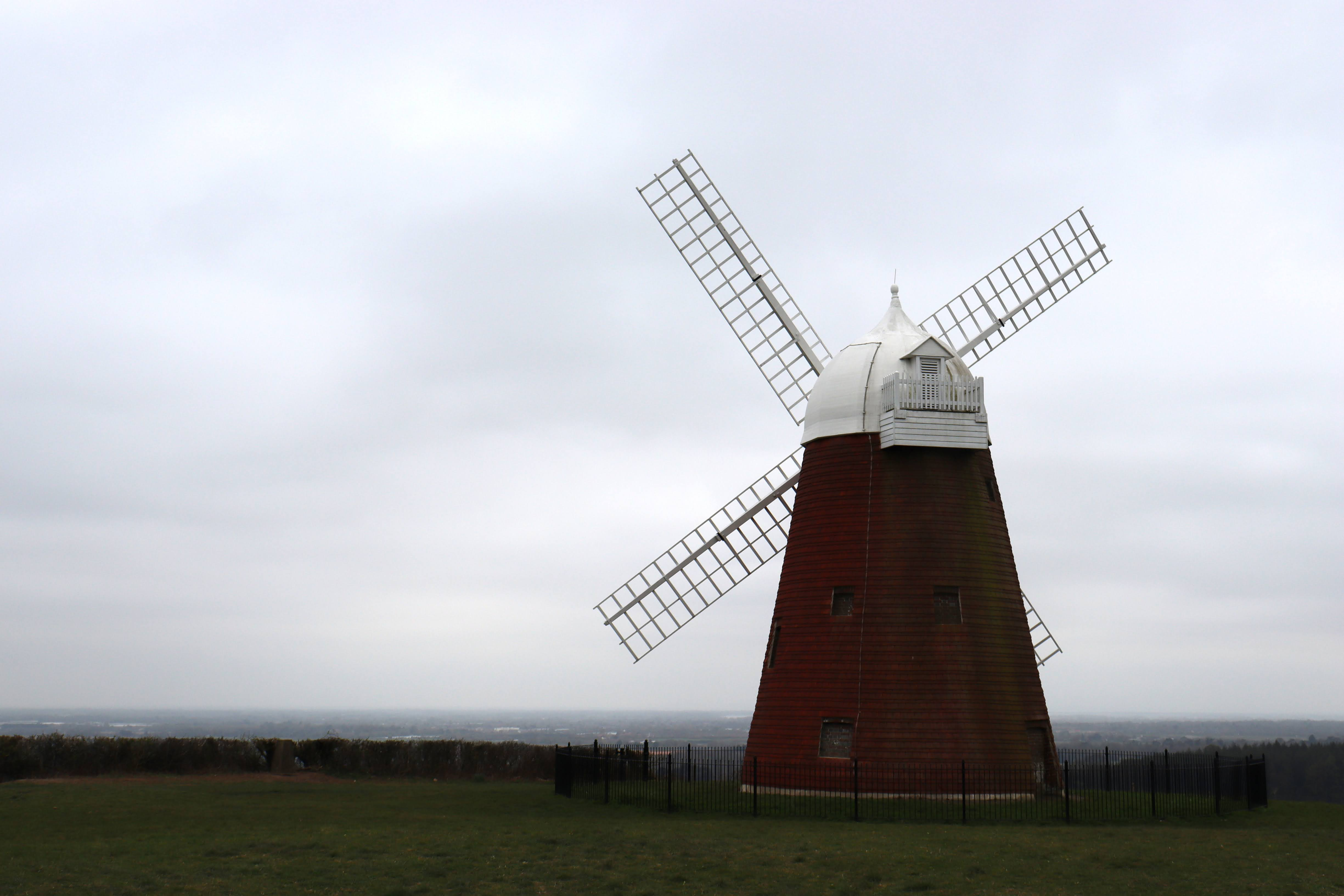 The red and white Halnaker Mill from the back. Surrounded by green grass and hills in the background.