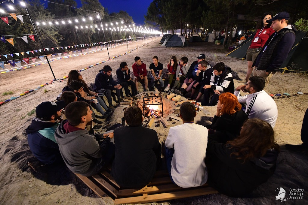 People sitting by a campfire at the Seaside Startup Summit in Sevan, Armenia