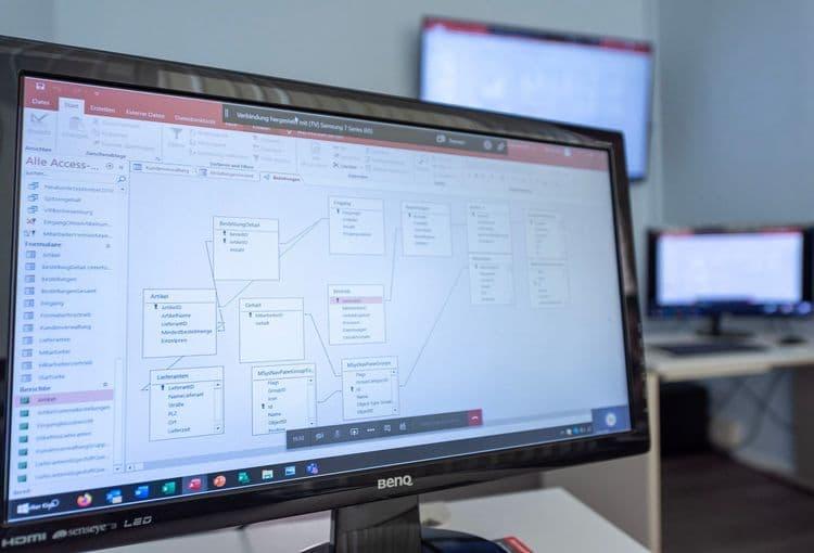 Im Vordergrund ist ein Bildschirm mit Access-Übungen aus unserem Access-Aufbaukurs zu sehen, im Hintergrund ist unser Schulungsraum mit Access-Lehrmaterialien zu erkennen