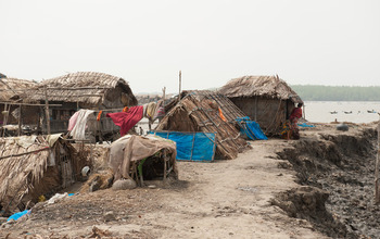 Bangladeshi villagers live atop a levee that's rapidly eroding following a series of river floods.