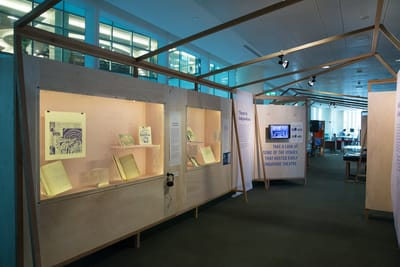A photo of an exhibition section. On the left wall, wall showcases with books and items are inside. There is a small TV screen displaying an image.