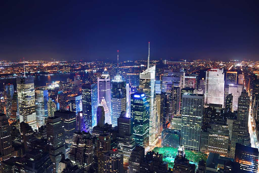 Aerial view of skyscrapers at night around Times Square, in Midtown Manhattan, New York City.