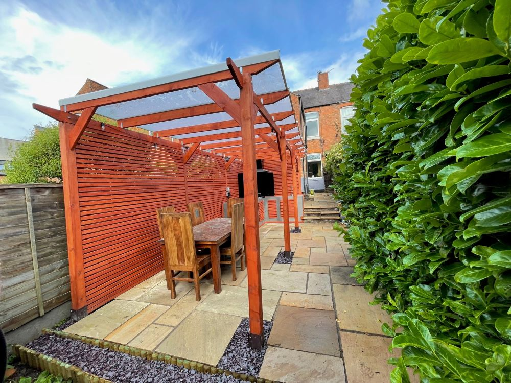 An example of a pergola with a kitchen area under it with seating.
