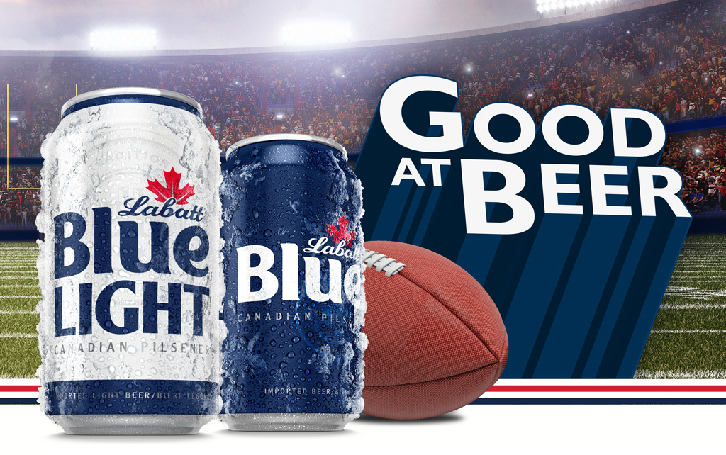 Text reads: Good at Beer. Image depicts a stadium with cans of Labatt Blue and a football in the foreground
