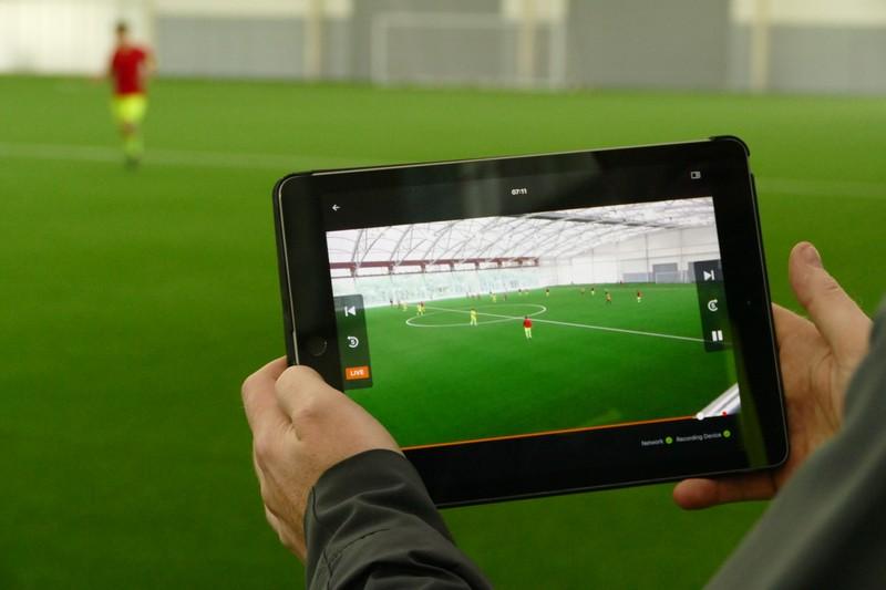 サイドラインからタブレットでサッカーの試合のリプレイを見ている男性