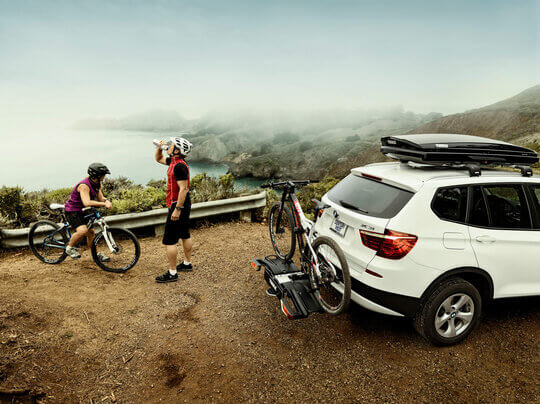 White SUV with roof box and bike carrier