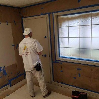 man taping walls