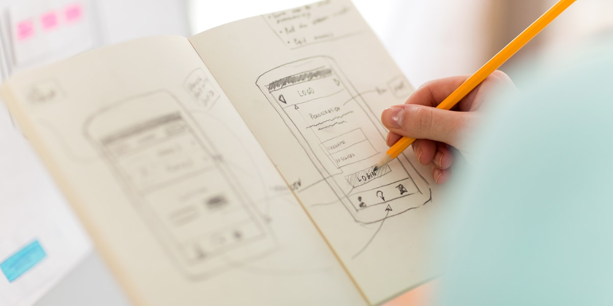 A UX designer sketching out a wireframe in a notebook