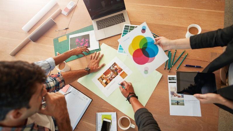Eine Gruppe junger Mitarbeiter sitzt an einem Tisch mit Laptop, Kaffeetassen, Stiften, Ausdrucken und Bildern und diskutiert eine Markenstrategie.