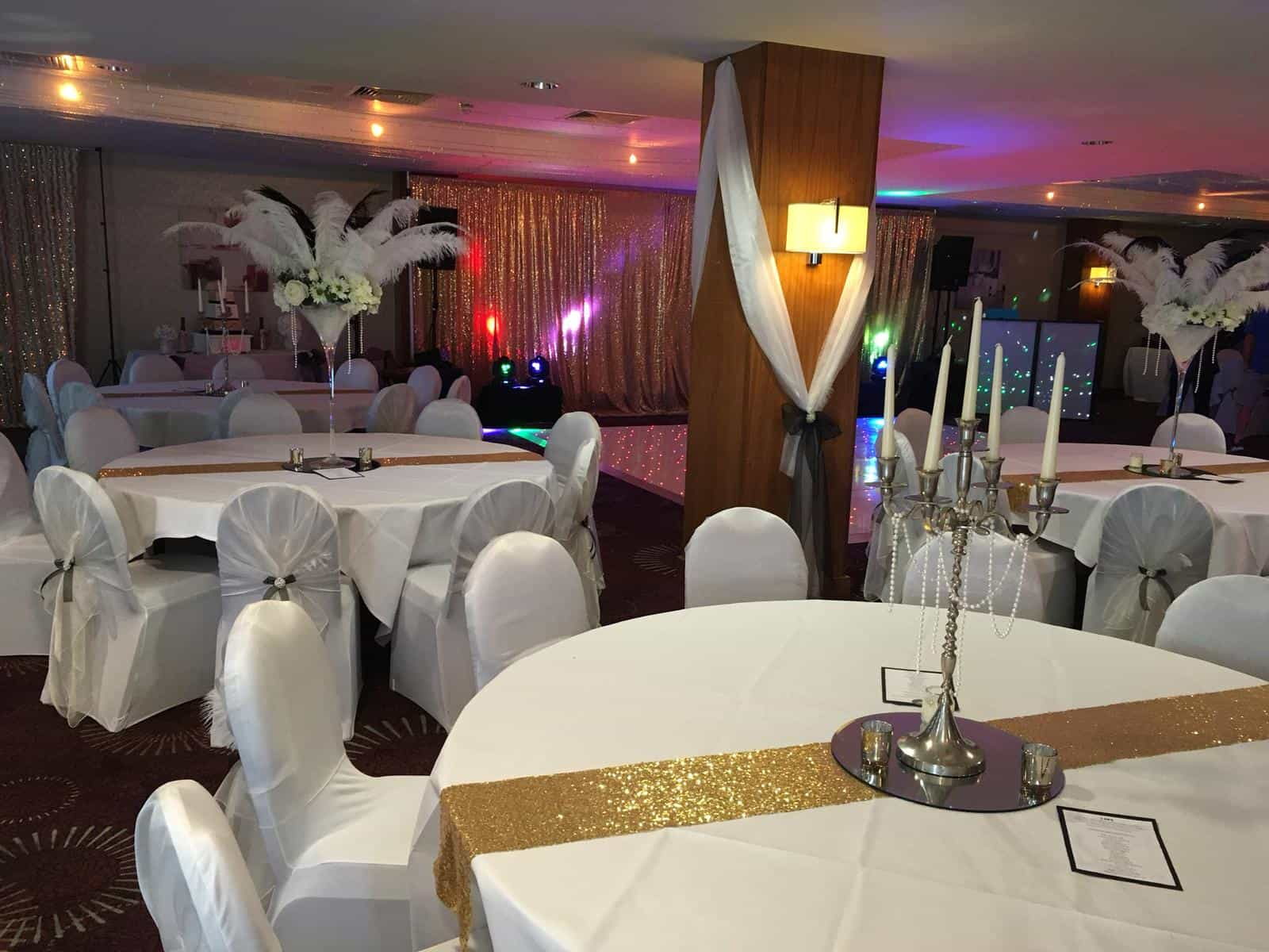 Wedding tropical theme with sprawling white palm leaves coming out of tall martini vases with white table and chair linens