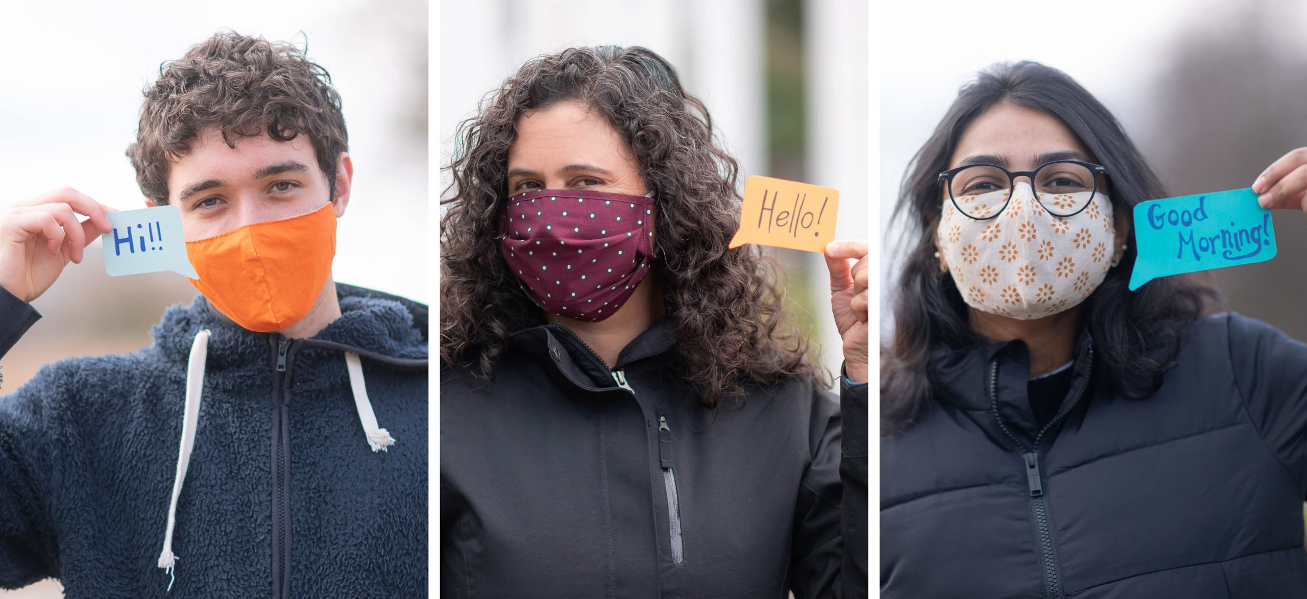 Three people wearing COVID-19 face masks say hello using signs