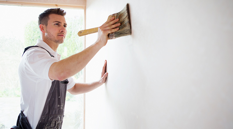 Image of a Local Heroes Painter and Decorator brushing a wall for dust