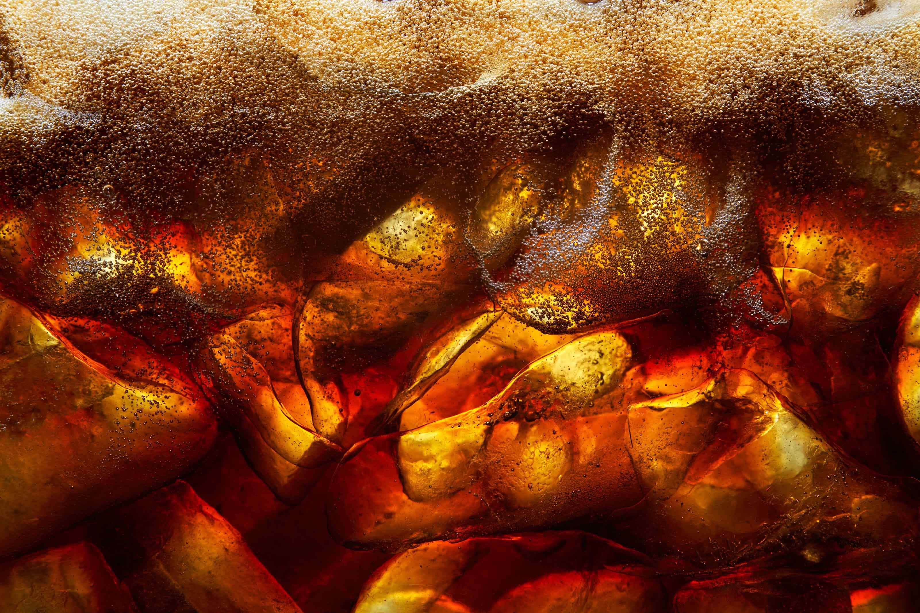 coke poured into ice with froth and bubbles back lit