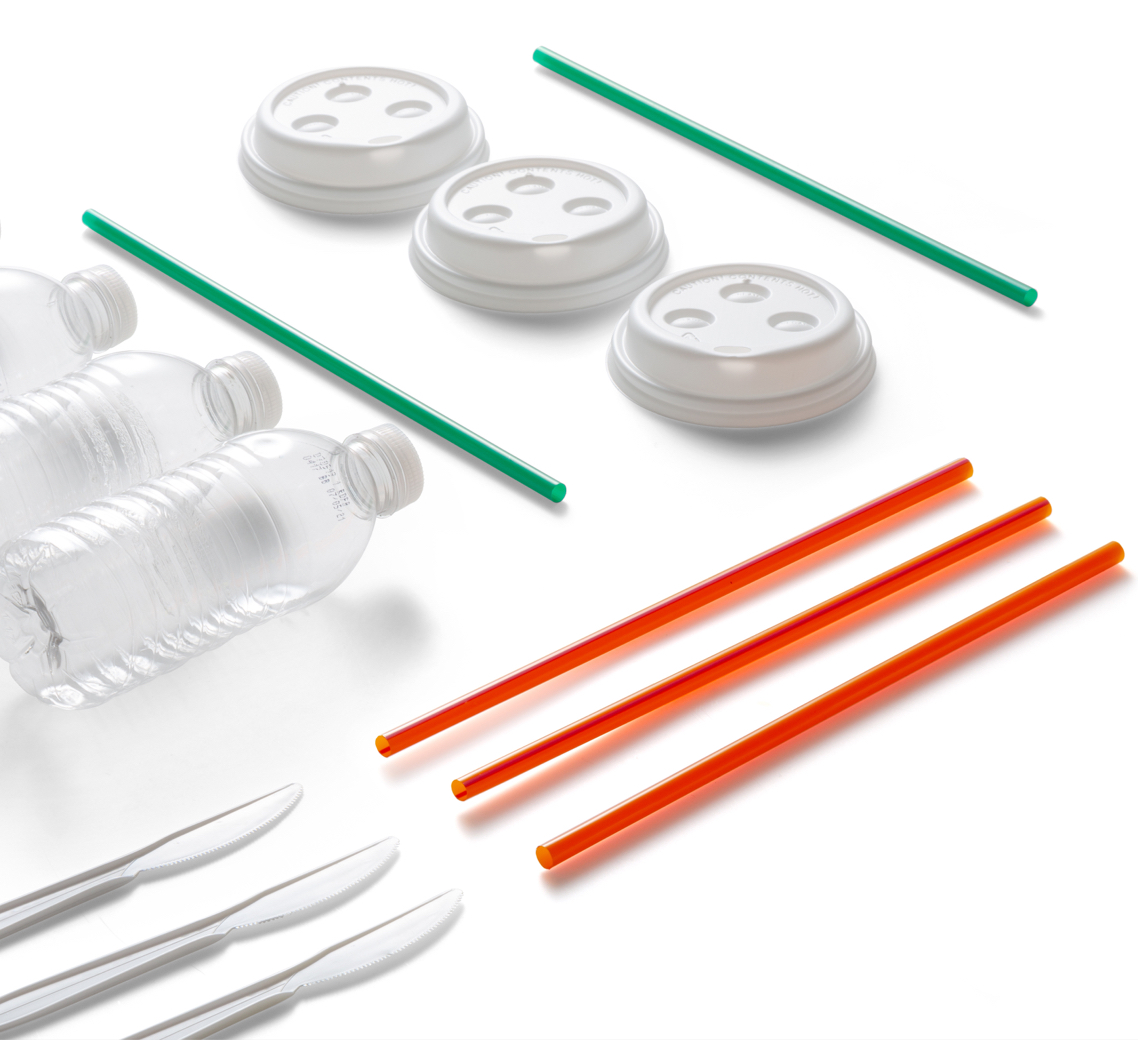 Plastic bottles, straws, knives, and coffee lids arranged on a white background