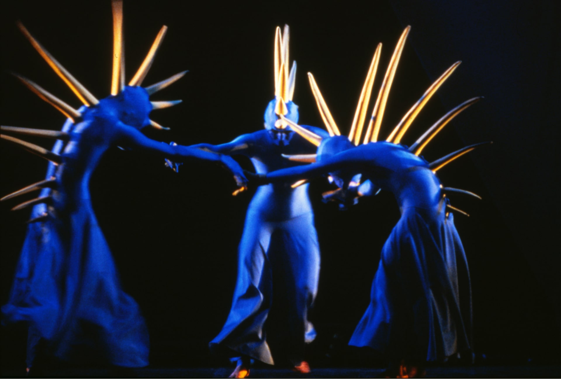 Three blue-garbed dancers with yellow spine spikes hold hands.
