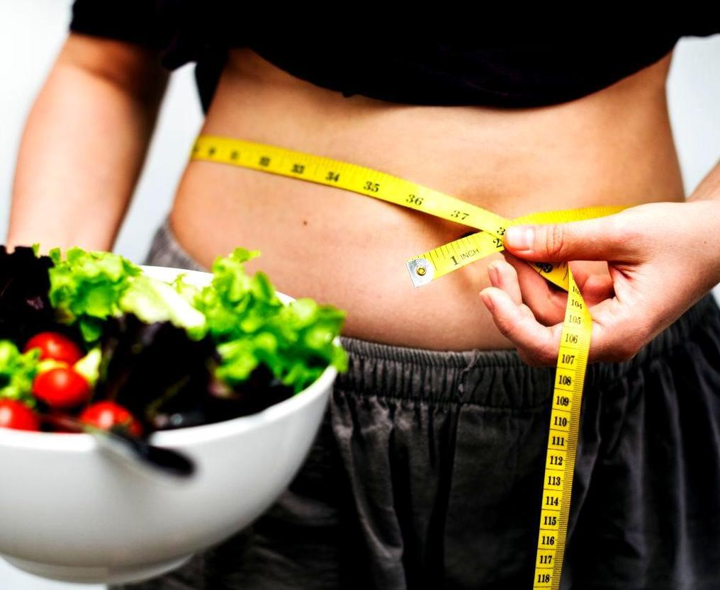 Person holding salad, measuring their waist