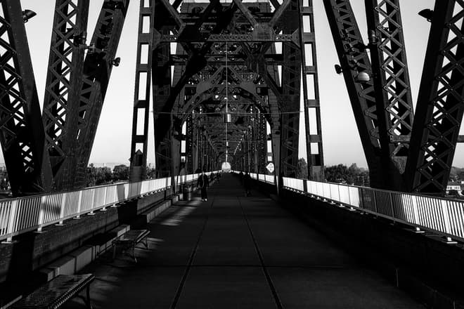 Looking north towards Indiana along a steel footbridge crossing the Ohio River. A large number of pedestrians are walking along the footbridge towards the photographer.