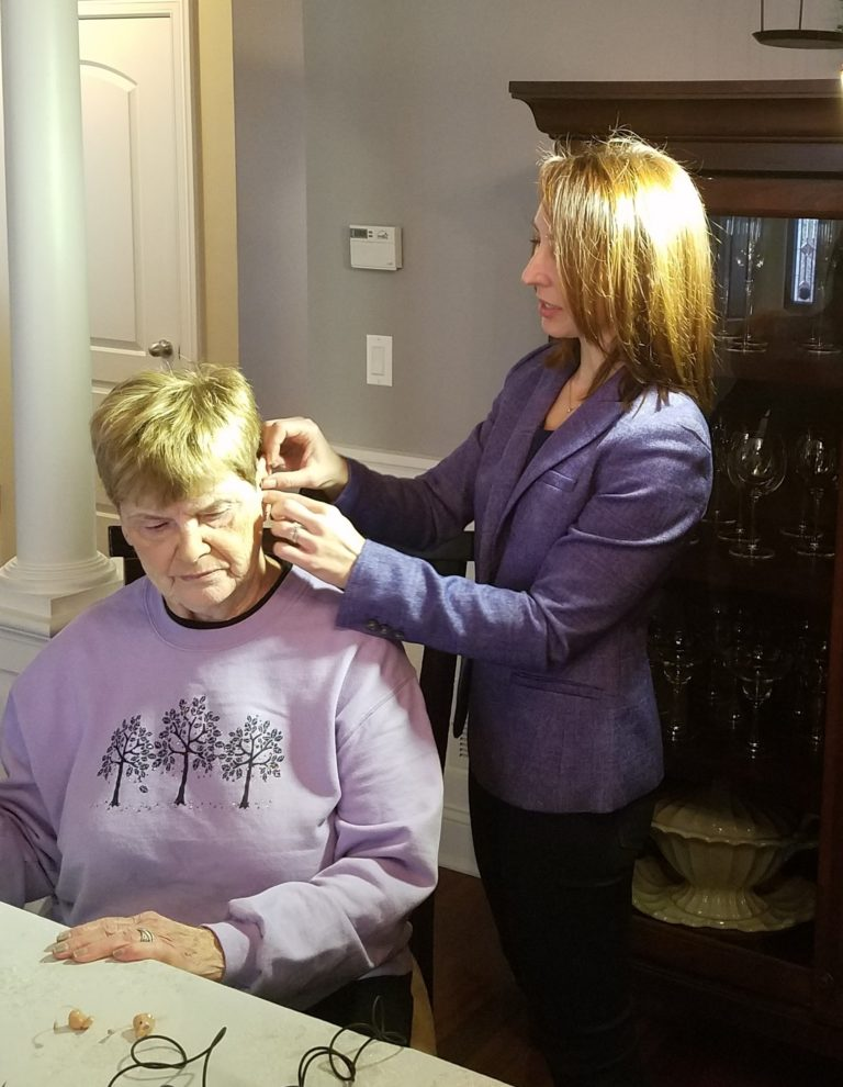 Dr. Corbett fitting a patient with a hearing aid